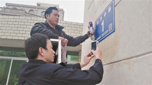晋江市的公安民警在安装二维码门楼牌(蔡福仁 摄)