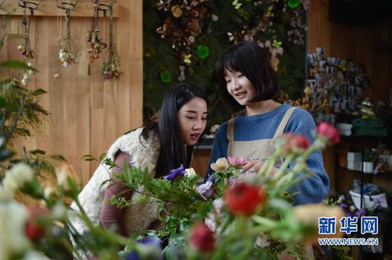 3月17日,陈莹莹(右)指导来自外地的创业班学员制作法式桌花。