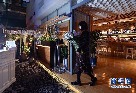 3月16日,陈莹莹在结束一天的教学后将花材收起,以便外面的咖啡店可以错峰使用工作室所在的区域。新华社记者 宋为伟 摄