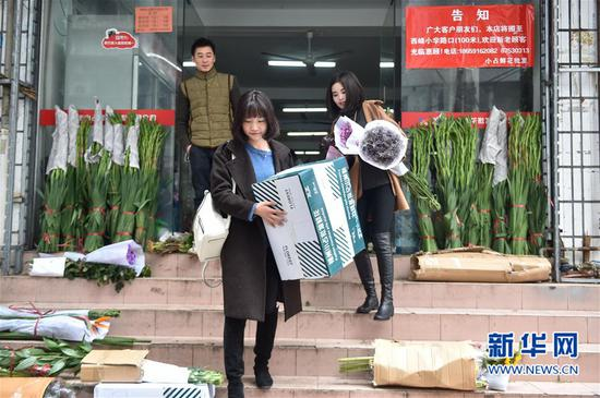 3月18日,陈莹莹(前)和吴佳英在花材市场搬运购买的花材。新华社记者 宋为伟 摄