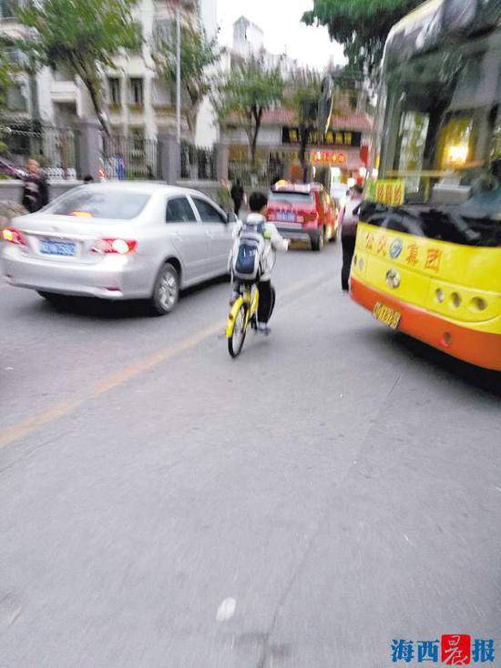 一名小学生在夹缝中骑行。