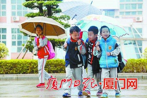 昨日下午突然下起雨,没带伞的孩子和小伙伴合撑一把伞。(本报记者 姚凡 摄)
