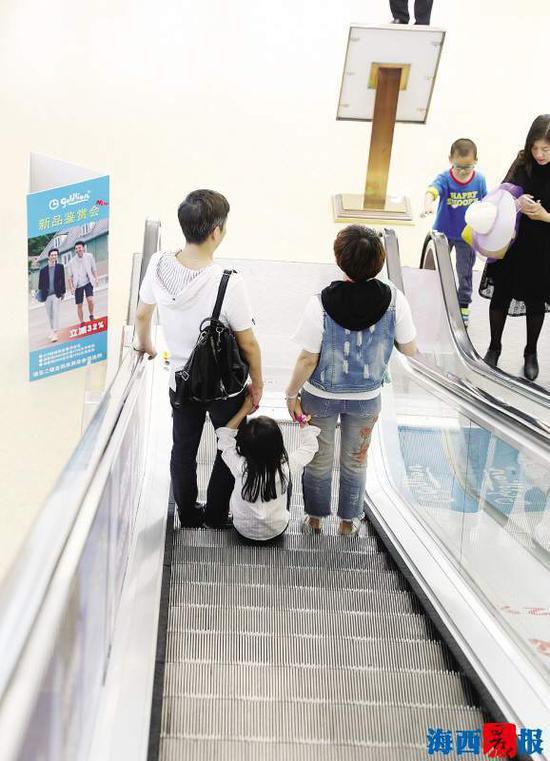 儿童乘自动扶梯时,家长要注意看管。记者 陈理杰 摄