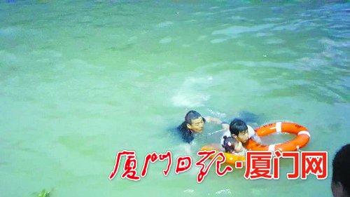 厦门轮渡有限公司员工推着父女二人往趸船游。
