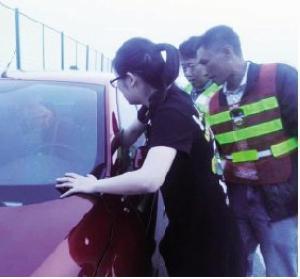 -女司机和救援队员正在施救。