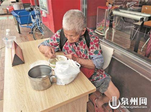 流浪阿婆正吃着高中生为她买来的饭