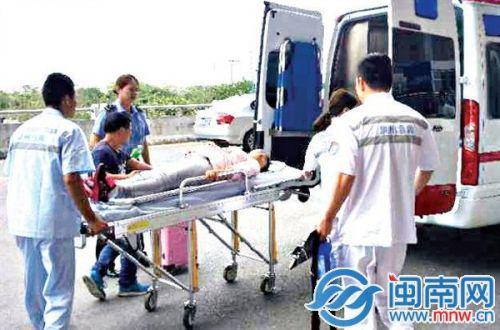 救护人员将孕妇抬上担架,送上救护车