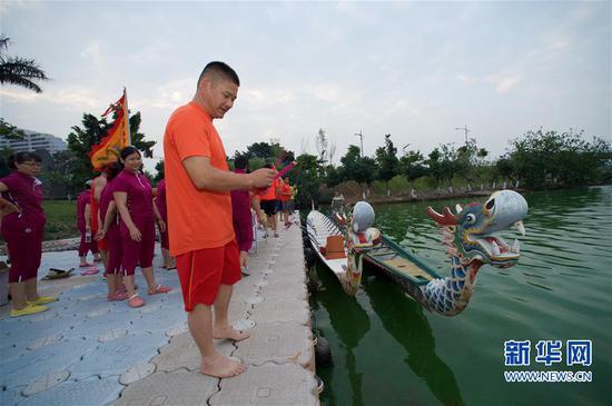高浦龙舟队队员王海乌在端午节龙舟祭祀活动上向海面抛撒篾香(2017年5月27日摄)。新华社记者姜克红摄