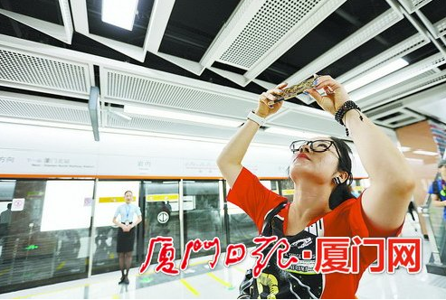市民拿起手机拍下车站的各种装饰细节。