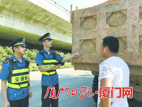 执法人员抓查污染路面的土方车。