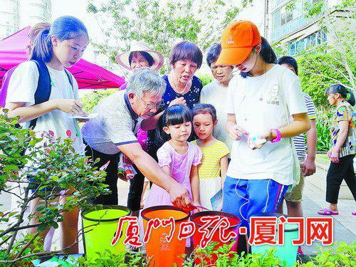 垃圾分类夏令营学员通过互动游戏,向居民宣导垃圾分类知识。(本报记者 吴海奎 摄)