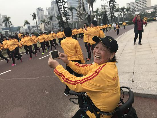 68岁的熊祖永高兴地给队友们拍视频。原来她因车祸下肢失去知觉,二十多年不能行走。去年开始跟借助轮椅跟大家一起锻炼,现在但她每天都能走6000-8000步。
