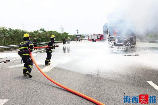 17日中午,一辆半挂车自燃,消防官兵在扑火。通讯员 陈远万 摄