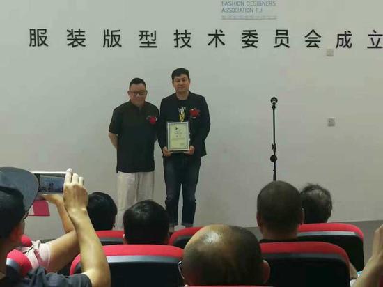 福建省服装设计师协会会长曾凤飞为首届主任委员殷磊颁发聘书
