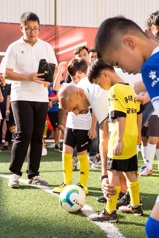 球星贝隆为小球员传授足球技巧。