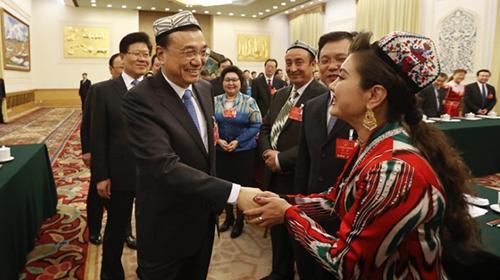 李克强新疆团审议带花帽 和每位代表握手