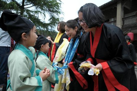图为身着汉服的小朋友、子女向母亲们行揖礼,并帮母亲戴上亲手制作的围巾