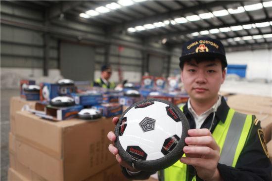 """图为宁波海关关员正在查看侵犯""""RUSSIA 2018""""商标权的电动足球 张佐 摄"""