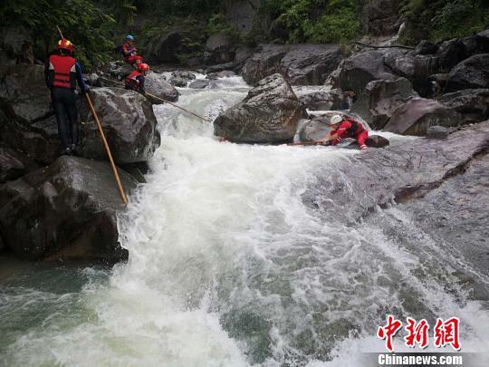 搜救人员在湍急的水流旁进行搜寻。 山福镇供图