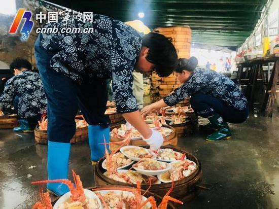 后厨的阿姨在刚出炉热气腾腾的龙虾上撒上葱姜等配料。