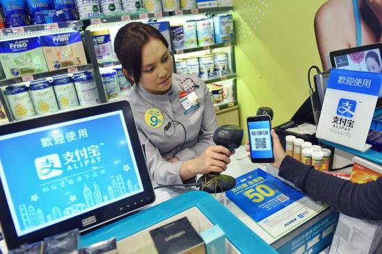 """图为""""支付宝HK""""在香港一家零售店进行扫码交易测试。新华社记者秦晴摄"""