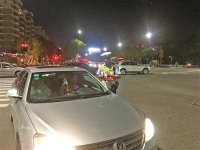 床图为海曙交警对违规使用远光灯的车主进行处罚。(王晓峰孙勇摄)