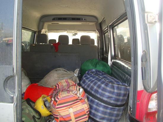 图为:7座的客车挤进13人,加上一大堆行李。
