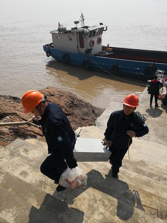 工作人员抬着100多斤重的5G设备上岸。 李立 摄