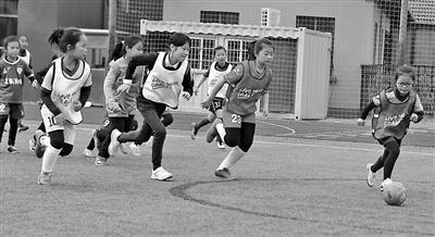小球员奔跑在绿茵场上。