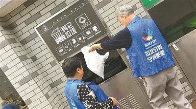 前天上午,柴国权、毛亚萍在垃圾房前忙着分类垃圾。(王博摄)
