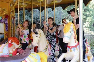 宁波儿童公园,小朋友开心地玩旋转木马。