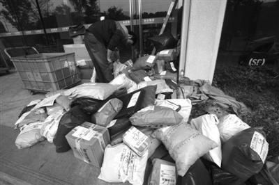 一写字楼下,快递员在整理快递物品。记者张培坚摄