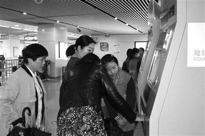 小志愿者在自助购票机帮乘客买票