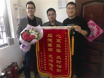 老人家属蒋先生(左一)拿着锦旗和鲜花致谢司机黄米富(中)通讯员供图