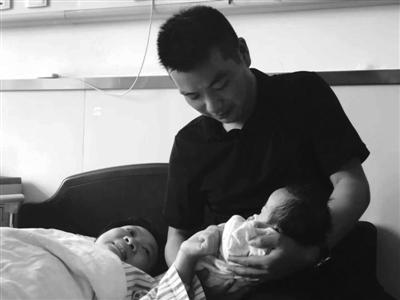 余女士和丈夫看着刚出生的孩子其乐融融 通讯员供图