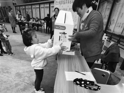 六岁的邹静然小朋友抱来榨汁机捐给共享驿站