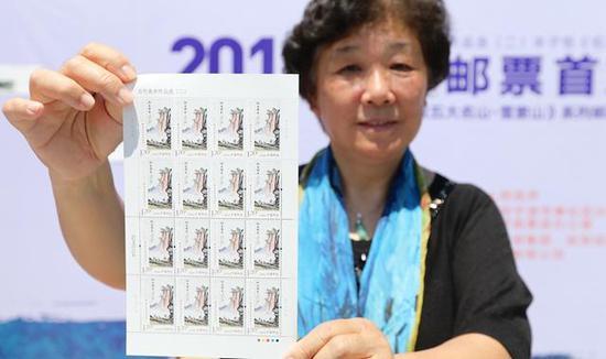 丰子恺的外孙女杨朝婴展示特种邮票《仰之弥高》。浙江新闻客户端 通讯员 章勇涛 摄