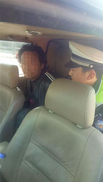 图为交警护送男子上警车离开 宁波高速交警供图