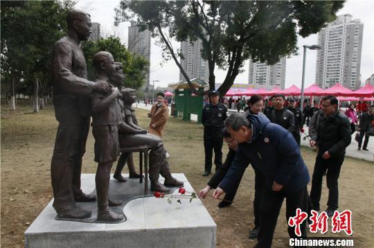 图为人们向雕塑献花 周松 摄