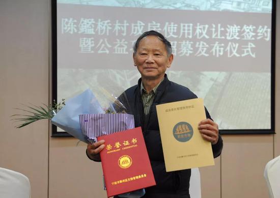 ▲陈家麟老人展示协议与荣誉证书