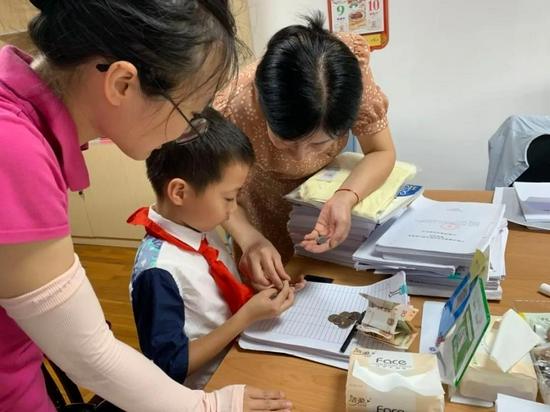 一名学生在家长的带领下,来到市慈善总会捐出自己储蓄罐里的钱。郭天放/摄