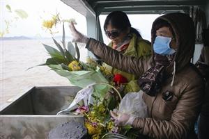 逝者家属把亲人骨灰和鲜花一起撒入大海