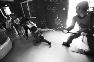 海曙区青少年科技活动中心科技体验一日游活动,小朋友在和机器人拔河记者 张培坚 摄