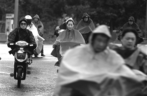 昨天傍晚,雨中赶路的市民 记者 贾东流 摄