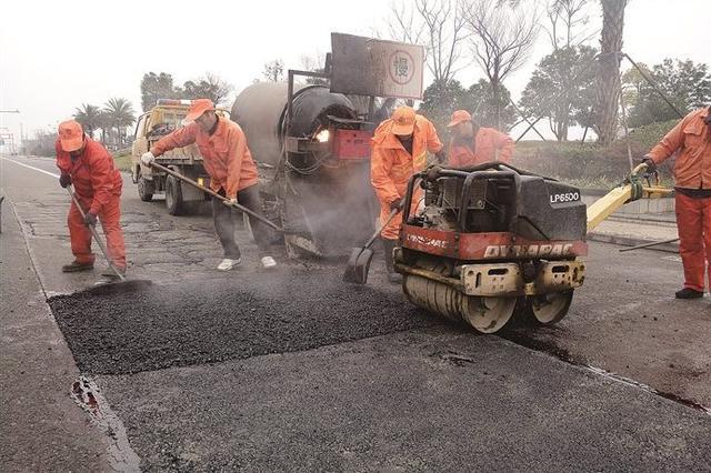 连日降雨路面易造成坑洞 奉化养护工人冒雨修补破损路面