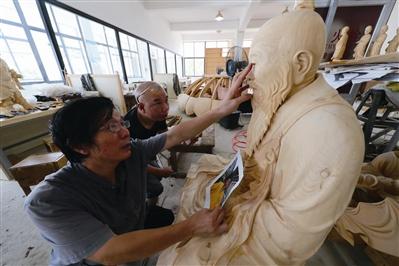 黄才良(左一)对徒弟的作品提出意见