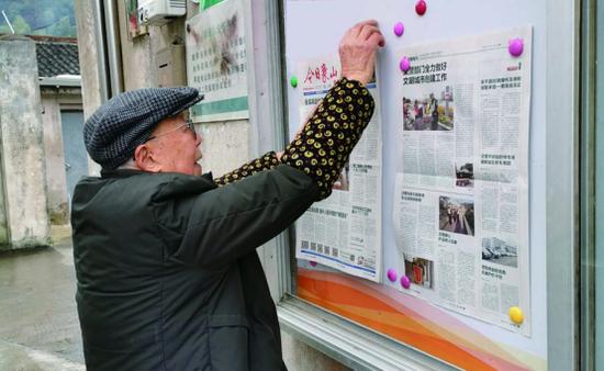 象山老人在村口阅报栏上张贴党报 二十二年风雨无阻
