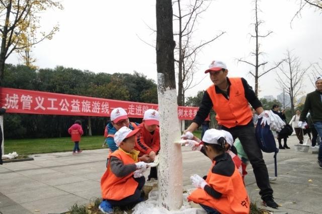鄞州义工为树木保暖过冬 弘扬绿色环保生态主题