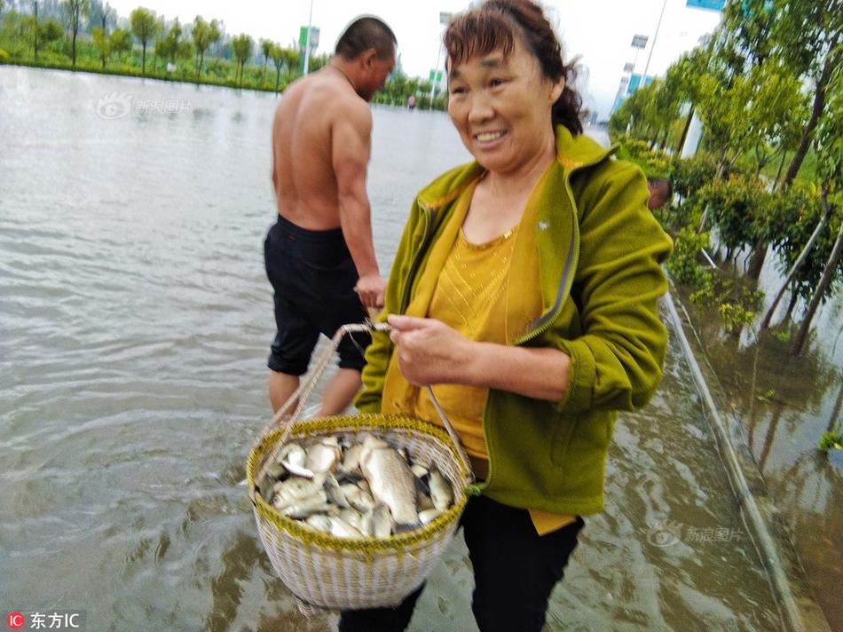 安徽淮北暴雨 市民在被淹道路上逮鱼