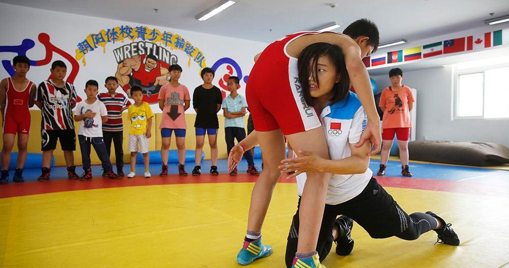 陶荣蓉正在朝阳区体校摔跤馆向参加摔跤训练的孩子们展示摔跤技巧.
